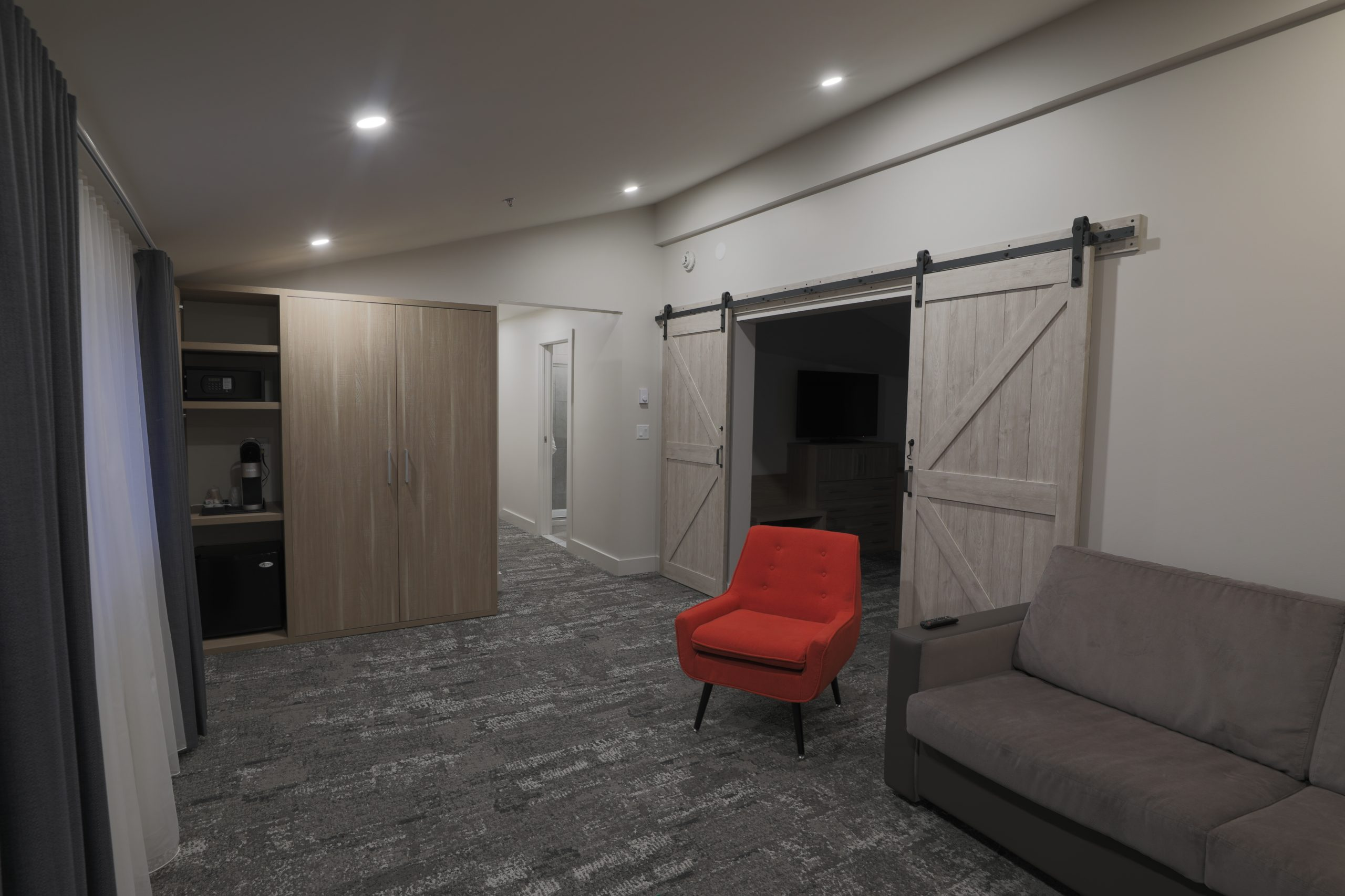 King Suite sitting area with barn doors leading to bedroom and small kitchenette area