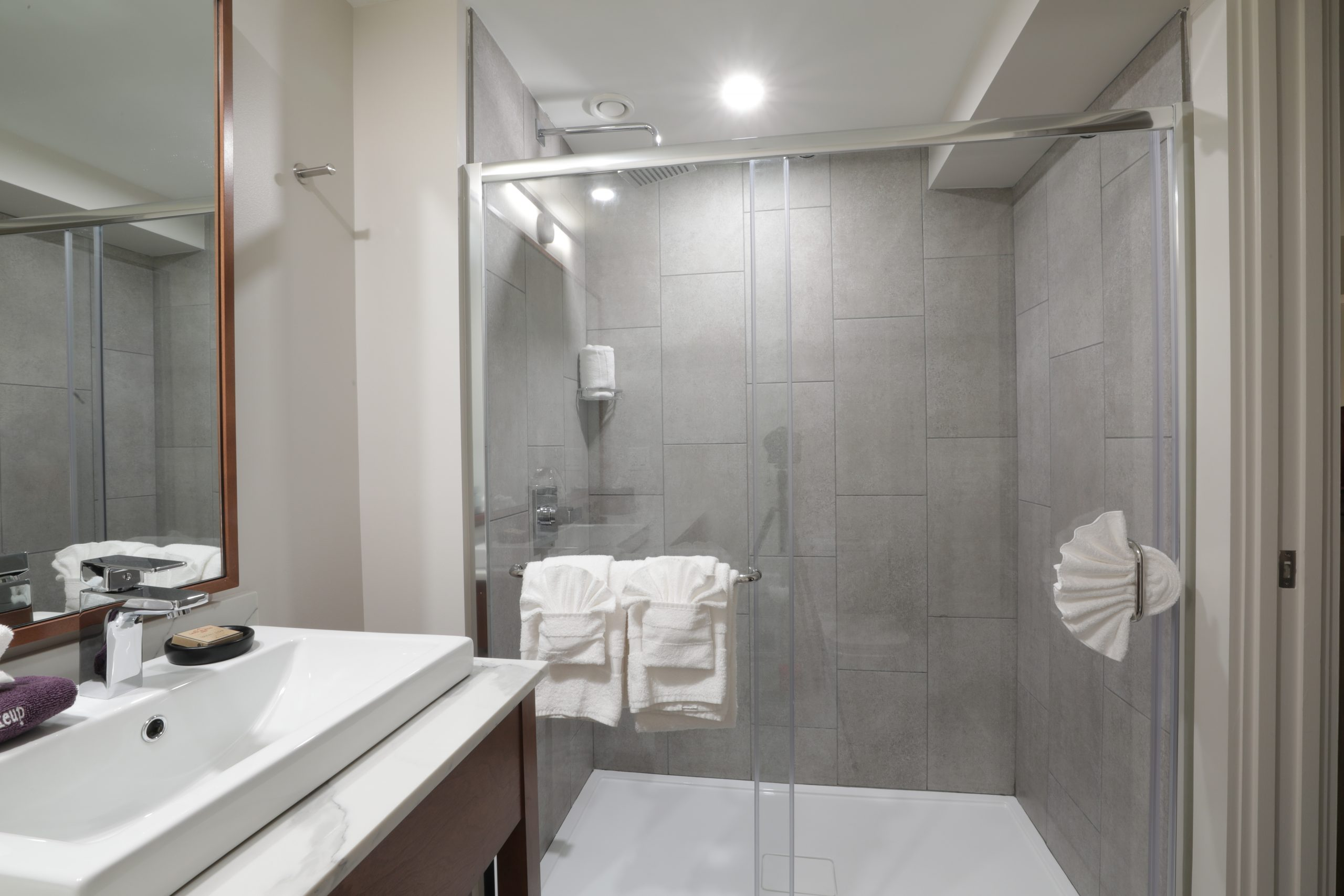 Glass walk in shower and large bathroom vanity and sink