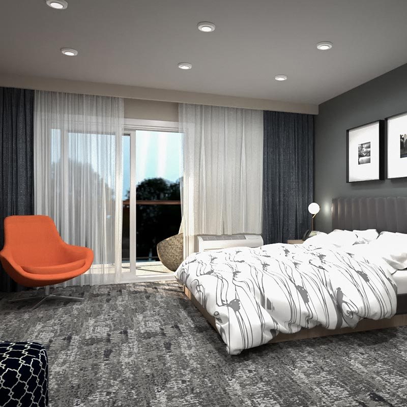 Hotel room with sliding door out to balcony, bed and orange chair