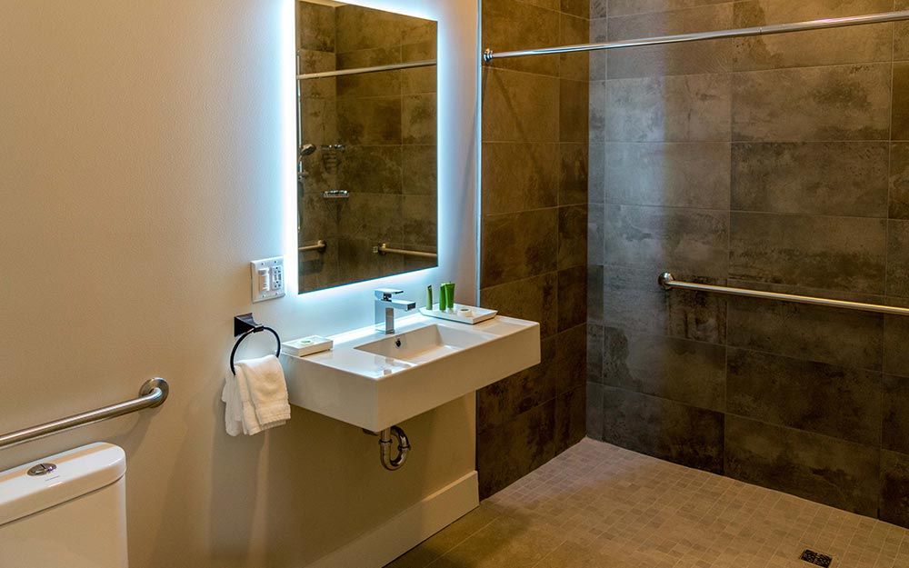 Bathroom with walk in shower and backlit mirror