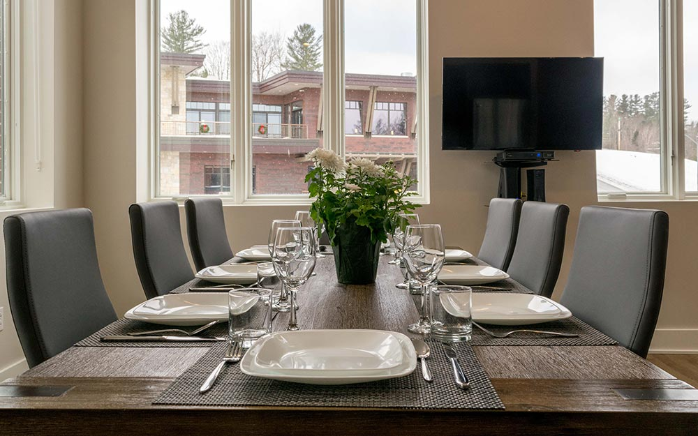 Dining room table with place settings and TV on wall