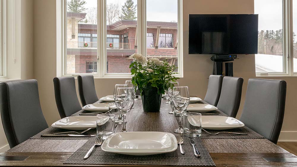 Set dining tables with TV on wall and large windows