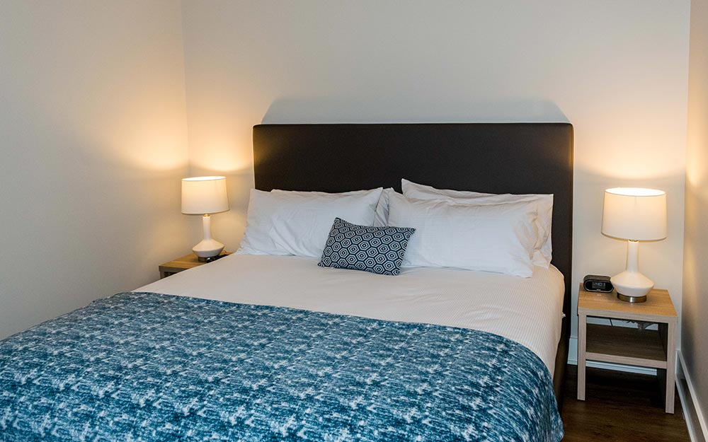 King bed with blue blanket and 2 nightstand with lights