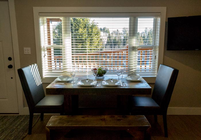 Dining table set with plates next to window