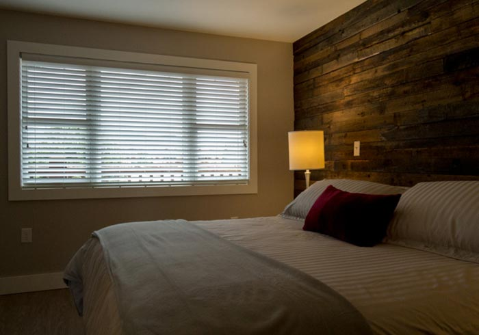 Bedroom with barn board accent wall and bed