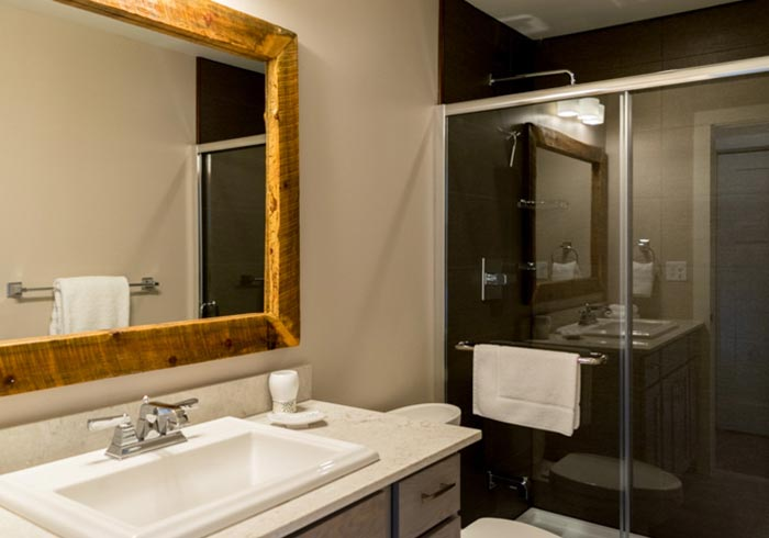 Bathroom with vanity, rustic mirror and glass shower