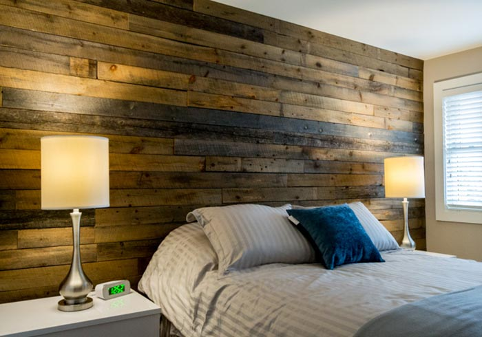 Bedroom with barn board wall with bed and nightstands with lamps