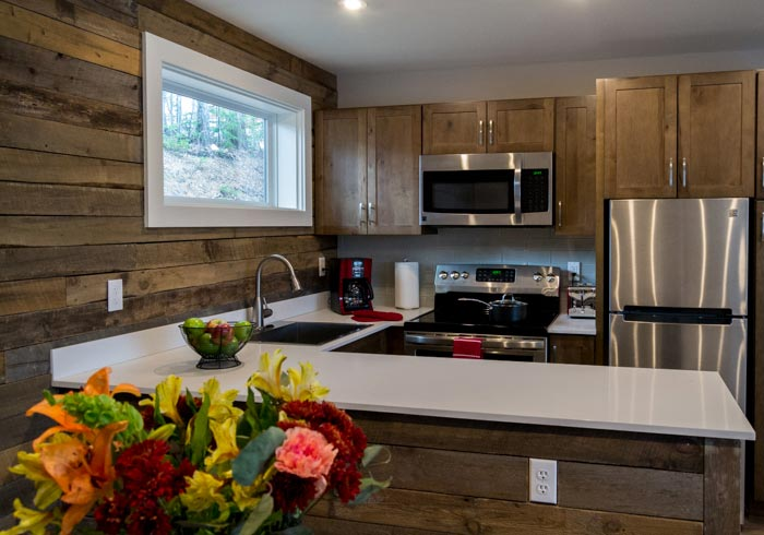 Barn board wall in kitchen with white counter tops and stainless applicances