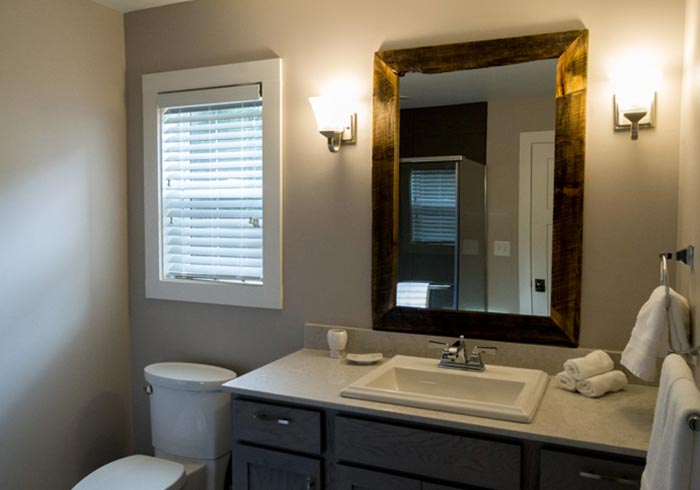 Bathroom with vanity and wood framed mirror