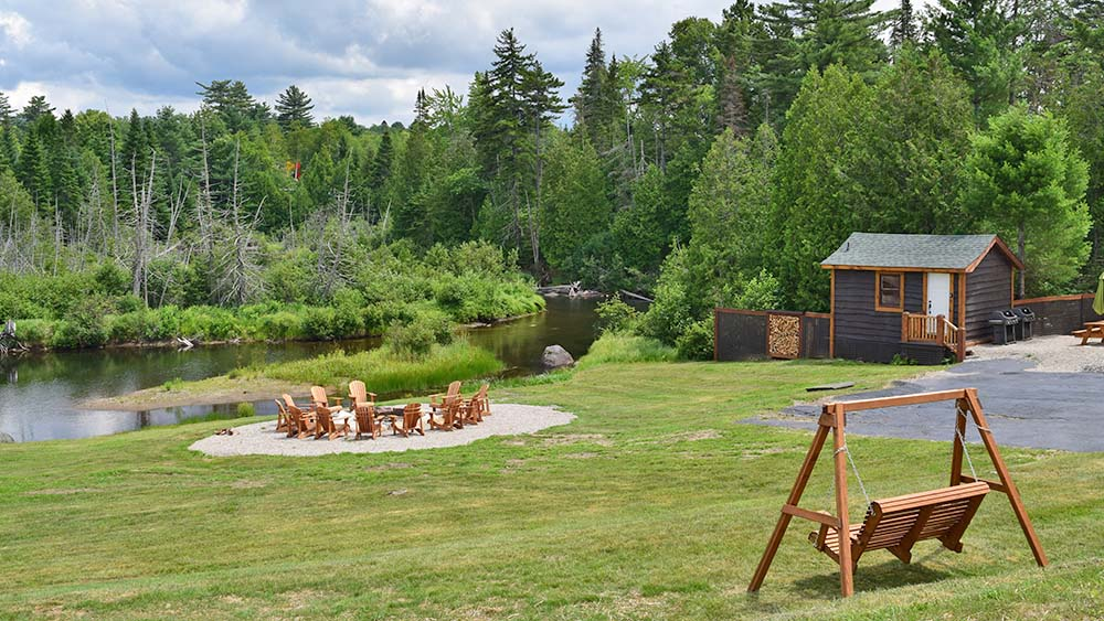 Cabin, firepit with chairs a wood swing