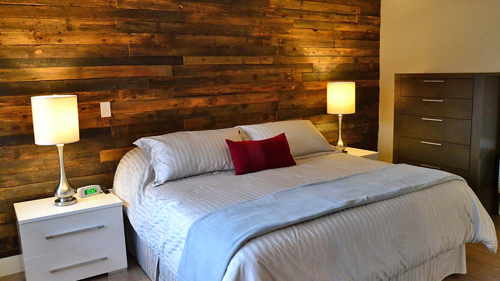 Bedroom with wood plank wall