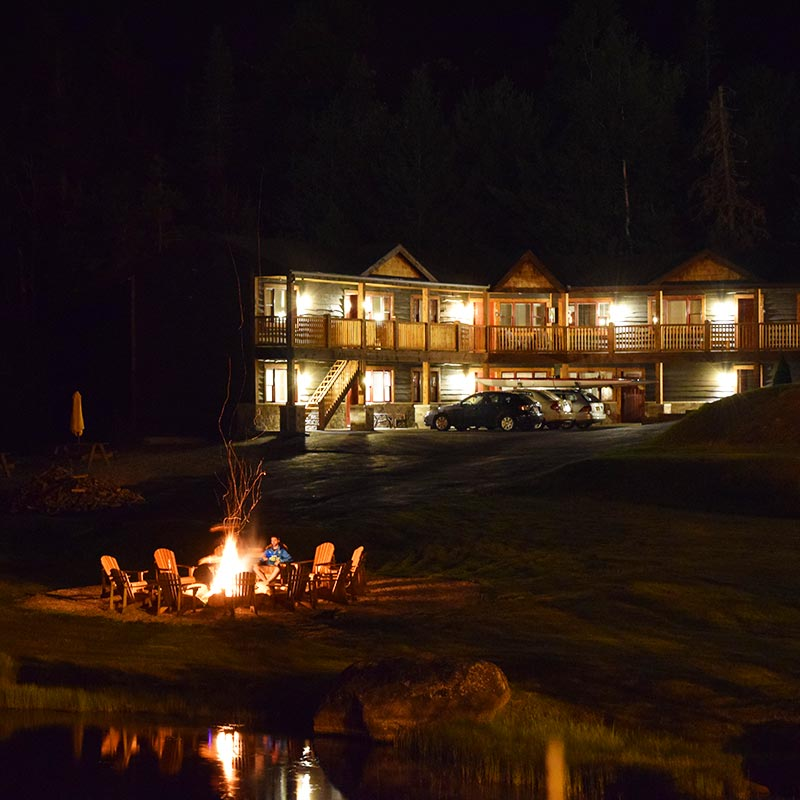 2 story motel lit up at night with bonfire in yard
