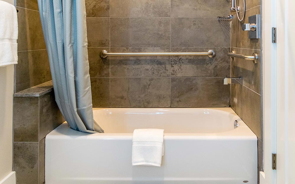 Bathroom with grey tiles and tub